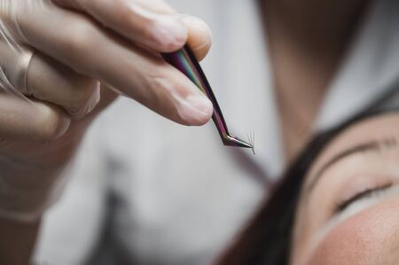Woman lies on eyelash extension procedure in a beauty salon. Lashmaker holds tweezers with a bunch of artificial eyelashes. Close-up of a craftsman in gloves.