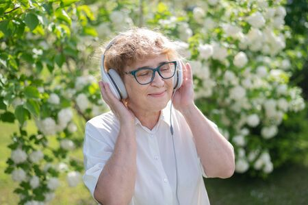 Happy old woman walks in the park of blooming apple trees and listens to music on headphones. A female pensioner is smiling and enjoying a warm summer day in the garden. Advanced older generation.