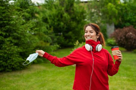 Red-haired woman in headphones and drinks coffee with a straw in the park and takes off a medical mask. The girl enjoys a free walk on a sunny summer day at the end of quarantine.