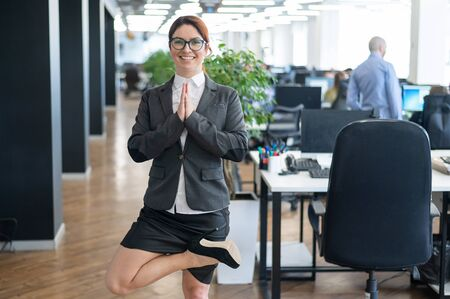 A pacified business woman doing yoga in an open space office. A red-haired smiling female employee in a casual suit and glasses stands in a tree pose at the workplace. Meditation and relaxation. Banco de Imagens