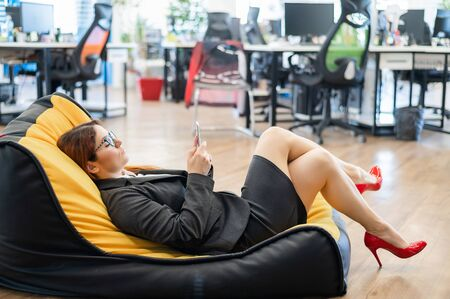Business woman resting in a cozy bag chair and enjoys mobile. Female Manager at a break in a modern office. Caring for the convenience of employees. Beanbag in the workplace
