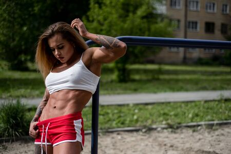 Young woman bodybuilder posing near parallel bars. Outdoor sports in isolation. A strong and muscular girl is engaged in fitness on a sports ground.