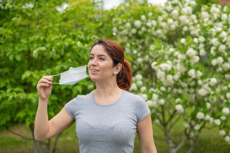 A woman in a gray T-shirt happily takes off her medical mask at the end of quarantine. A girl celebrates the end of quarantine while walking in a park. Free breathing without allergies.