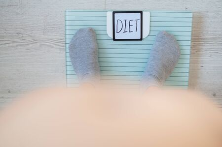 Top view of female legs in socks standing on the floor scales. The inscription on the diet display. A woman with a bare stomach and obesity should lose weight.