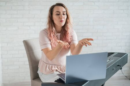 A friendly woman plays the electronic piano and conducts a video blog on her laptop. Stay home. Musical instrument teacher. Distance learning music quarantined.