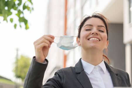 A woman in a business suit walks outdoors during a break and takes off a medical mask. The insulation is over. Quarantined finished coronavirus defeated. The office clerk happily returns to work.