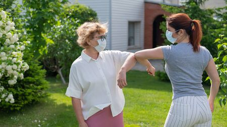 Two masked women greet their elbows in the park. An elderly woman and her daughter maintain social distance during the coronavirus epidemic. A new way of shaking hands. Apple trees are blooming.