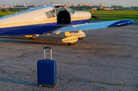 A blue suitcase and a parked small private jet. Quadruple airplane with propeller for air taxi. Self travel concept. Imagens