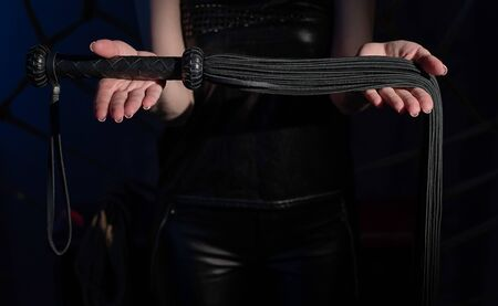 Black leather lash in the hands of an unrecognizable woman. Cropped photo of bdsms toys. Punishment and pleasure. A woman stands in the dark and holds a whip in her palms. Banco de Imagens - 149634140