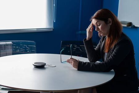 Tired office employee in glasses and a suit with a headache in an empty conference room. Business woman after unsuccessful negotiations with partners and colleagues in the boardroom. Problems at work.