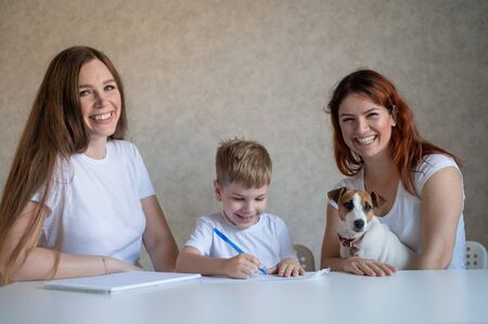 Happy family stays at home. Two women help the boy do school homework. Lesbian couple sitting at the table with their son and a cheerful puppy. Same-sex marriage with a child. Distance learning.