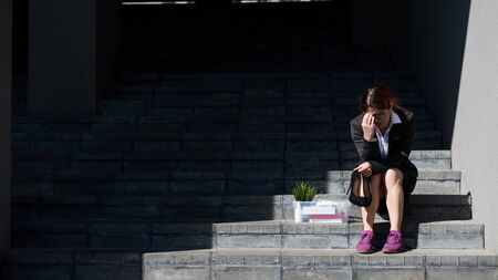 Depressed woman dressed in medical mask is fired and is sitting on the stairs with a box of personal belongings. Female office worker in suit and sneakers outdoors. Unemployment in the economic crisis