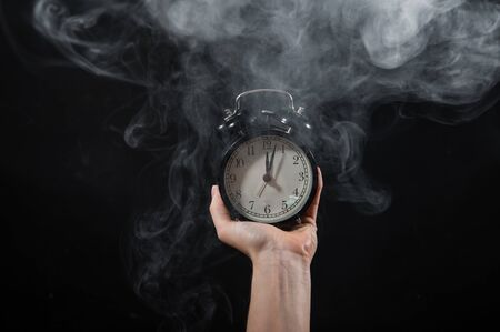 Close-up of a female hand holding a clock on a black background in smoke. Alarm clock at midnight in a mystical fog.