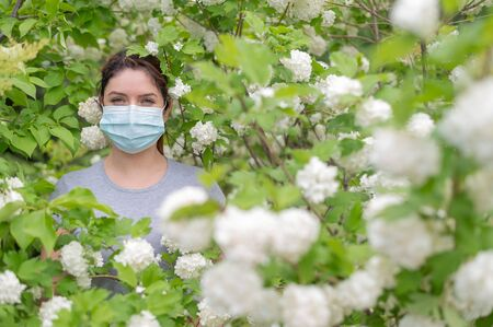 An unhappy red-haired woman in a medical mask stands next to a blossoming apple tree in a park. Seasonal allergic rhinitis. The girl suffers from an allergy to pollen.