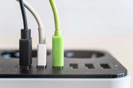 Modern convenient multi-port usb charger for devices. Close-up of multi-colored cables in a power outlet. Macro. pluged in. Stock fotó