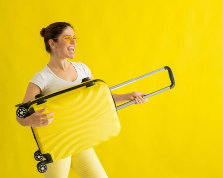 Smiling woman in sunglasses fooling around and holding a suitcase like a guitar on a yellow background. An excited girl in anticipation of a summer vacation trip simulates playing a string instrument.