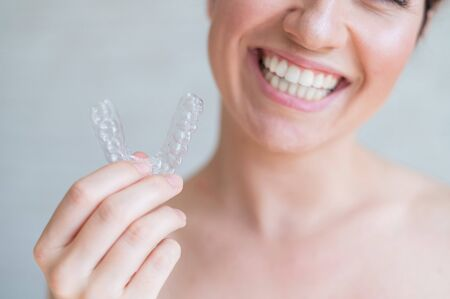 Close-up of orthodontic silicone transparent teeth aligner in female hands. A woman with a perfect charm smile holds a removable night retainer. Bracket for teeth whitening. Cropped photo.