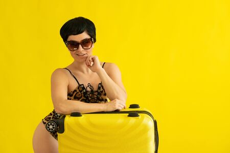 Portrait of an attractive woman in a one-piece leopard swimsuit and sunglasses with a suitcase on a yellow background. Seductive brunette in a monokini is ready to travel to the sea. Summer vacation. Standard-Bild