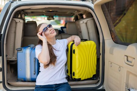 European woman in sunglasses packs her bags for a car trip. Beautiful happy girl sitting in the trunk of a car and ready for travel. Yellow suitcase with things for summer vacation. Фото со стока