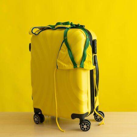 A candid mini-bikini of the coloring of the Brazilian flag hangs on a suitcase on a yellow background. The concept of a summer beach holiday. A woman is going on a trip to the sea