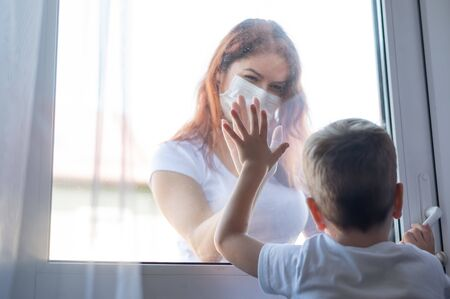 Social distance. A woman in a medical mask communicates with her son through a window. The girl on the outside leaned her hand against the glass door. Little boy isolated. Coronavirus epidemic.