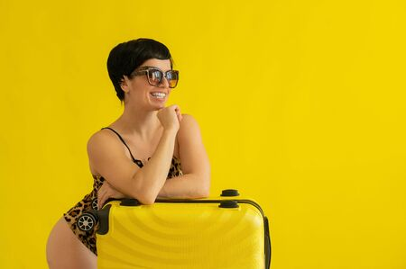 Woman posing in one leopard swimsuit and sunglasses with a suitcase on a yellow background. A brunette with a dazzling smile in a monokini packed her luggage and is ready for a beach vacation.