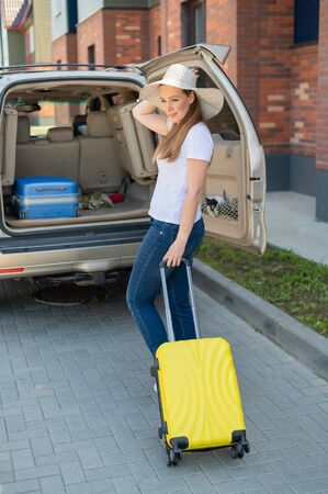 European woman in a hat alone packs her bags for a car trip. Beautiful happy girl loads a suitcase in the car trunk. Yellow luggage for summer holidays. Фото со стока