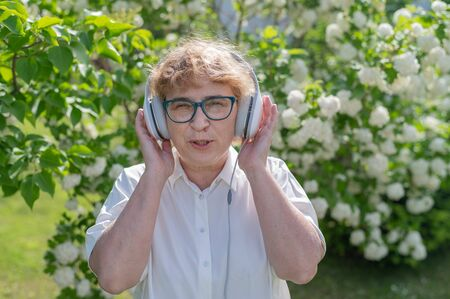 Happy old woman in headphones and dancing and singing in a park of blooming apple trees. An active female pensioner is enjoying a warm summer day. Grandma listens to music on a smartphone. Фото со стока