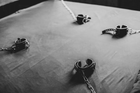 BDSM Leather handcuffs for role-playing games on a gray sheet. Bondage for carnal pleasures. Domination and submission.