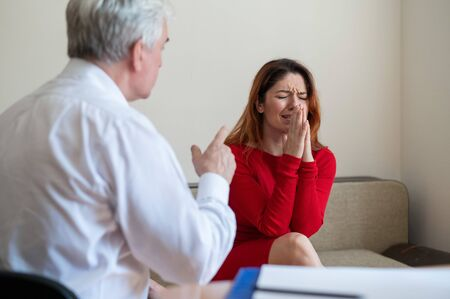 A frustrated crying woman holds her palms over face at a session with a male psychologist. Mature psychotherapist talking to a female patient with depression and neurosis. Mental health treatment.