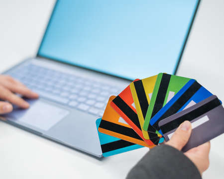 Close-up of female hands with many plastic credit cards. A woman holds several bank debit cards and makes purchases on the Internet on a laptop. The concept of online shopping with a loan.