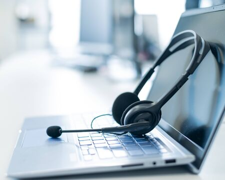 Call center operator desktop. Close-up of a headset on a laptop. Help desk. Workplace of a support service employee. Headphones with a microphone for voip on a computer keyboard Standard-Bild