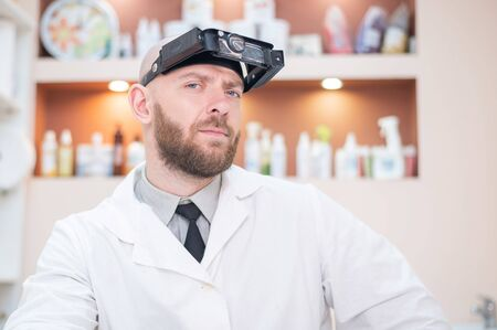Male bearded doctor in a medical coat and with a magnifying head strap w lights sitting on the desk. Optometrist equipment. Medical office.