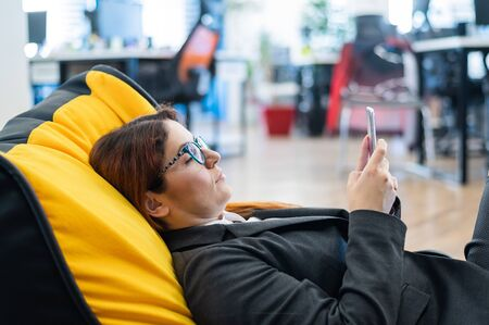 A business woman in a suit is resting while sitting in a comfortable chair bag and taking a selfie. A female employee uses a smartphone and relaxes while lying on a bean chair during a break at work.