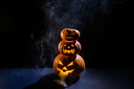 A spooky pyramid of jack-o-lantern in the dark. Glowing scary smirk carved in a pumpkin. Traditional halloween decorations. Horizontal greeting card or banner.