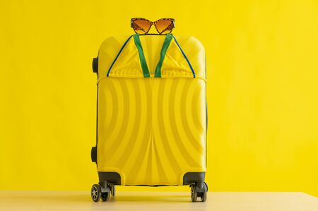 Yellow suitcase on wheels with tiger sunglasses and a mini bikini on a yellow background in the studio. Set for a beach vacation. Copy space. No people. Summer vacation at sea.
