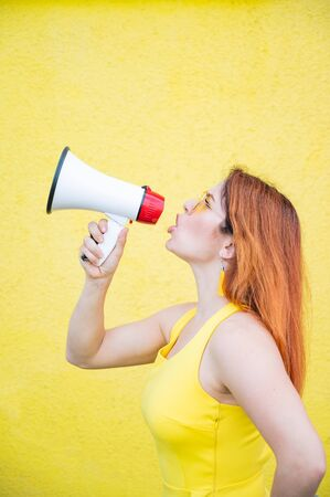 A woman in a dress with glasses and earrings stands in profile on a yellow background and shouts in a megaphone. Portrait of a girl holding a loudspeaker. Lady yells at a sound amplification device.