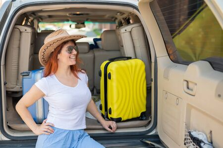Happy red-haired woman in a cowboy hat and sunglasses going on a car trip around the country. Girl sitting in the trunk with a yellow suitcase ready for summer vacation. Independent travel.