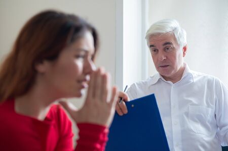 A frustrated crying woman holds palms in her face at a session with a male psychologist. Mature gray-haired psychotherapist talking to a female patient with depression and neurosis. Unbalanced psyche. Banque d'images