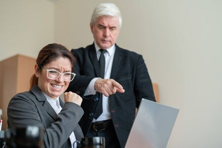 The male boss indicates the female subordinate a mistake. A gray-haired mature business man scolds an employee for unfulfilled work. An upset Caucasian woman failed.