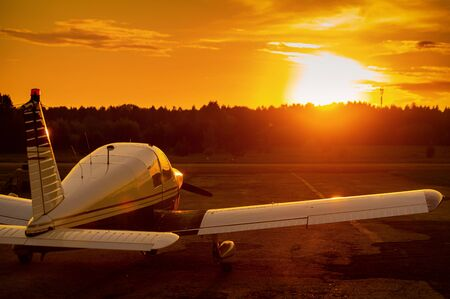 Quadruple aircraft parked at a private airfield. Rear view of a plane with a propeller on a sunset background.
