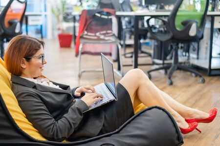 Business woman sits in a cozy chair bag and typing on a laptop. Female Manager works in a modern office. Caring for the convenience of employees. beanbag in the workplace.