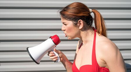 Red-haired Caucasian woman in a red bikini shouting into a megaphone against a background of a gray corrugated wall. Girl in a swimsuit with a loudspeaker. Summer vacation. Foto de archivo - 150386528