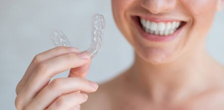 Close-up of orthodontic silicone transparent teeth aligner in female hands. Unrecognizable woman holding a removable night retainer. Bracket for teeth whitening. The perfect smile. Cropped photo.
