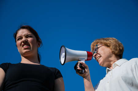 The conflict of generations. An emotional elderly woman shouting at her daughter in a megaphone. An elderly mother swears at a middle-aged woman on a loudspeaker on a blue background.