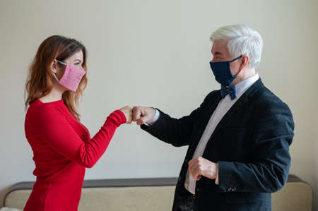 A mature gray-haired man in a suit and a red-haired middle-aged woman in a red dress is wearing masks and greeting fists. Colleagues greet while respecting social distance. 写真素材