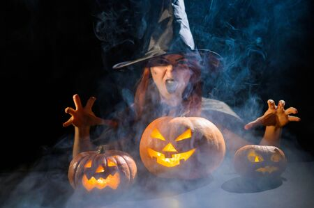 An ominous witch in a hat conjures over a jack-o-lantern. Traditional halloween characters. Mystical fog creeps over pumpkins with carved terrible faces. An evil witch casts a spell. Zdjęcie Seryjne
