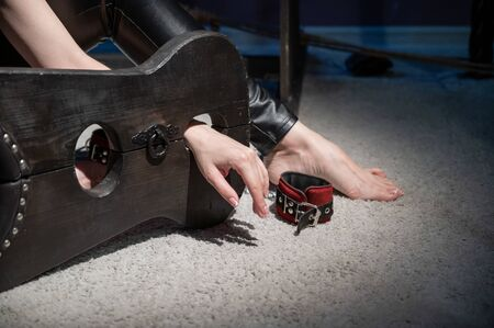 Female hands in wooden shackles during role-playing games. Shameful pillar and leather cuffs for sex. BDSM Domination and punishment. 스톡 콘텐츠