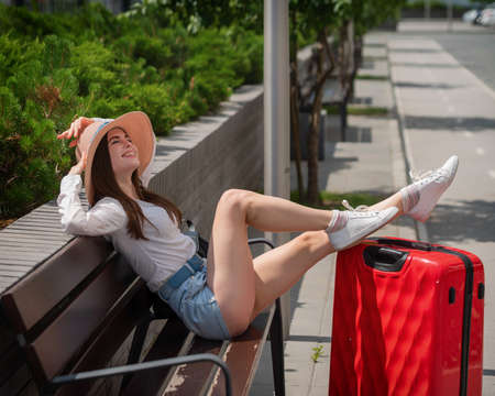 Beautiful brunette in shorts and a hat sits on a bench stretched out legs on a large red suitcase. Caucasian woman folded her feet on a luggage bag outdoors. Girl enjoys a trip in the park on a sunny. Banque d'images