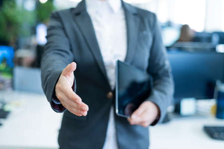 Woman office worker holds out her hand for greeting. Faceless business lady is holding a digital tablet and a handshake in an agreement to a successful transaction.